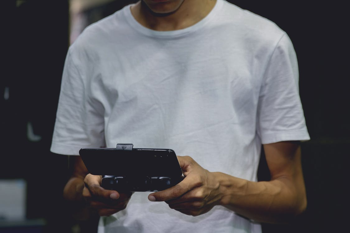 A Smartphone Game Controller On A Person's Hand