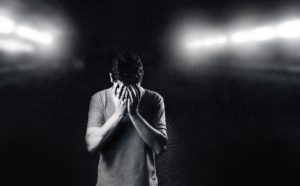 black and white photo of a man with his hands covering his face