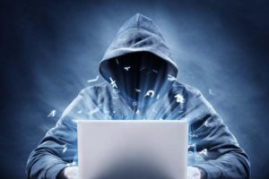 A photo of a hooded figure behind an open laptop.