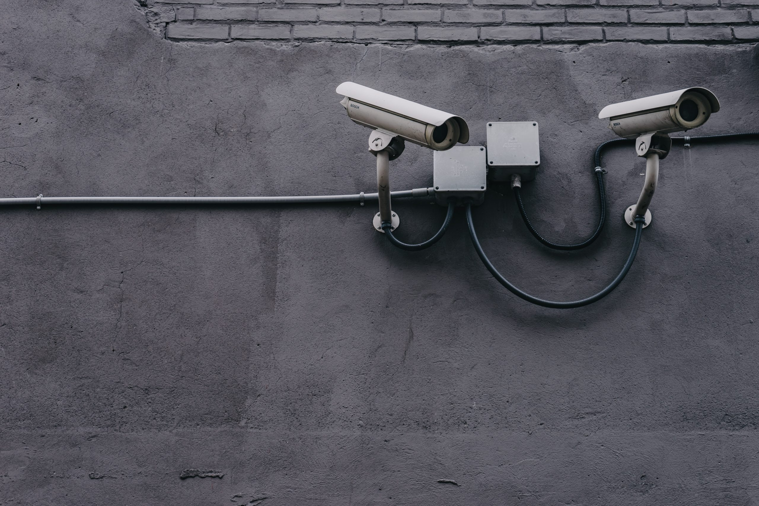 Two security cameras point to the right against a gray background.
