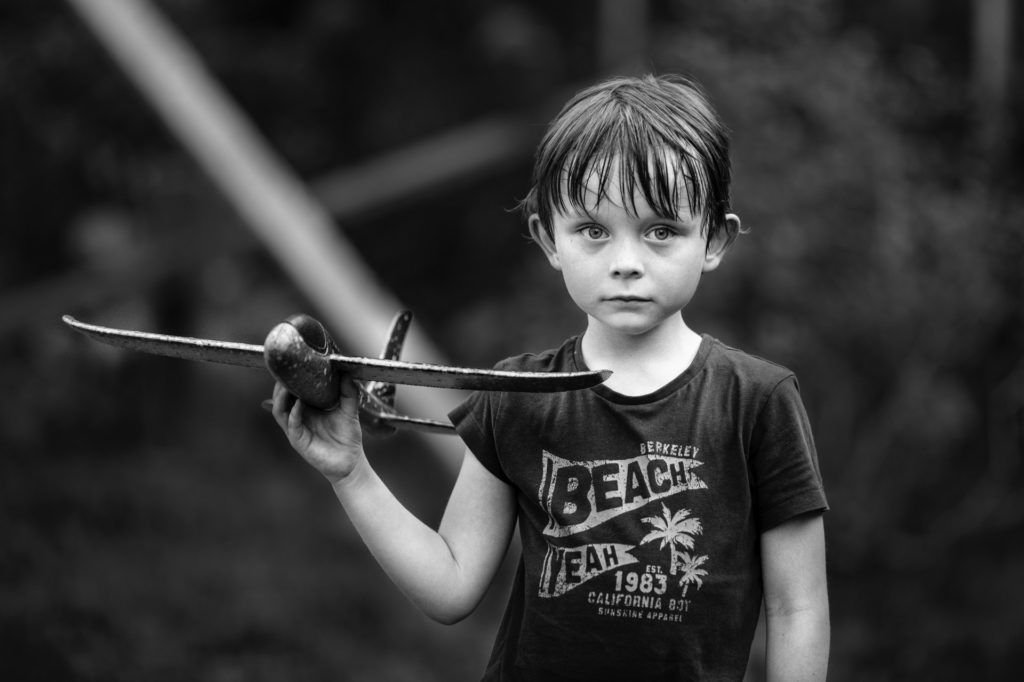 A photo of a young boy, outside, holding a toy airplane.