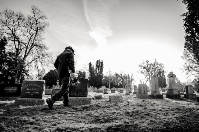 A photo of an elderly plan walking across a cemetery carrying a bouquet of flowers in the morning.