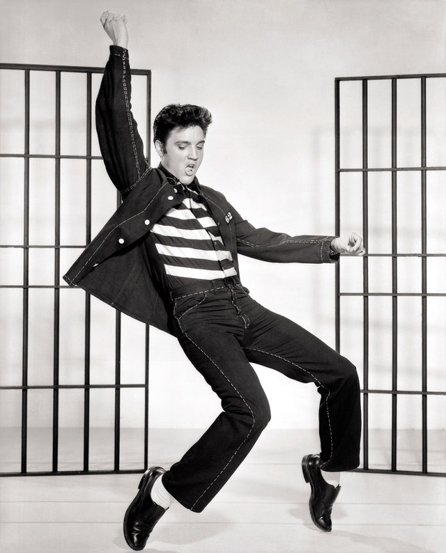 A photo of Elvis Presley, doing an iconic dance move with one arm in the air, the other arm extended from his side, his mouth open, his eyes lowered, and his knees bent with his feet upright on their toes.
